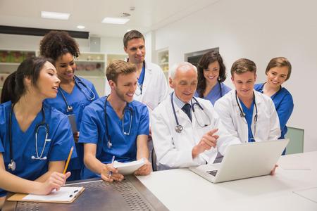 profesor: Estudiantes de medicina y profesor usando la computadora port�til en la universidad