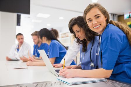 estudiantes medicina: Estudiante de medicina sonriendo a la c�mara durante la clase en la universidad Foto de archivo