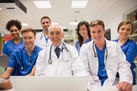 estudiantes medicina: Estudiantes de medicina y profesor usando la computadora portátil en la universidad
