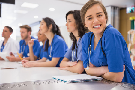 apprentice: Medical student smiling at the camera during class at the university Stock Photo