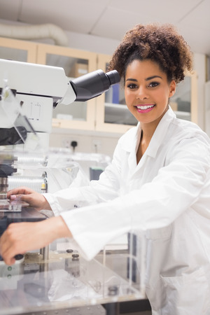 science scientific: Pretty science student using microscope at the university