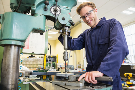mechanical men: Engineering student using large drill at the university