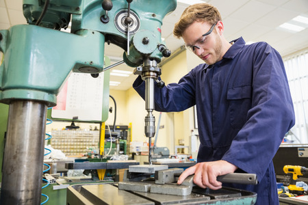 boiler suit: Engineering student using large drill at the university