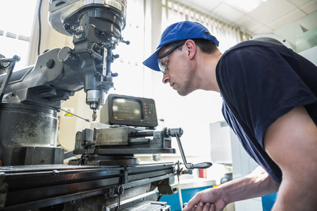 ingeniero: Ingenier�a estudiantil utilizando taladro grande en la universidad Foto de archivo
