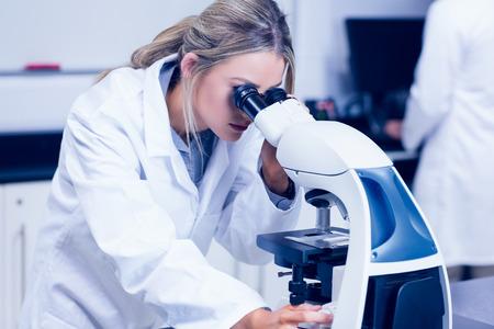 lab coat: Estudiante de la ciencia que mira a trav�s del microscopio en el laboratorio de la universidad