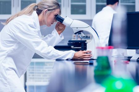 bata de laboratorio: Estudiante de la ciencia trabaja con el microscopio en el laboratorio de la universidad Foto de archivo