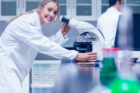 estudiantes medicina: Estudiante de la ciencia trabaja con el microscopio en el laboratorio de la universidad Foto de archivo