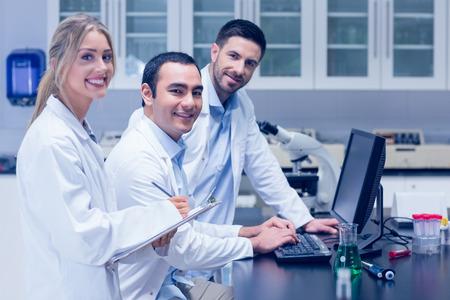 bata de laboratorio: Los estudiantes de ciencias que trabajan juntos en el laboratorio de la universidad Foto de archivo