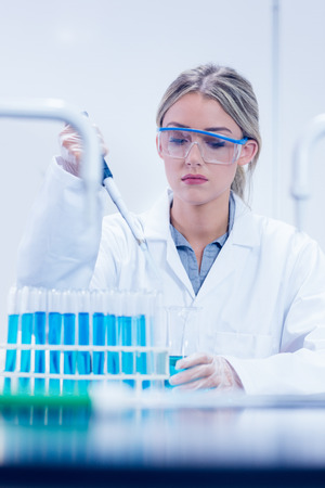 biochemist: Science student using pipette in the lab at the university