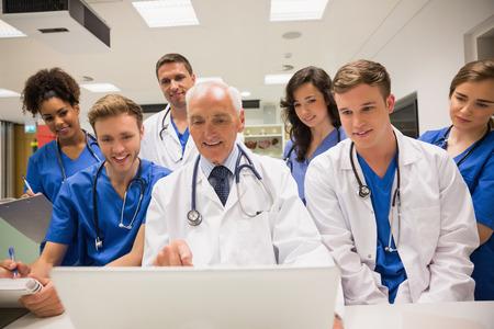 Estudiantes de medicina y profesor usando la computadora portátil en la universidad
