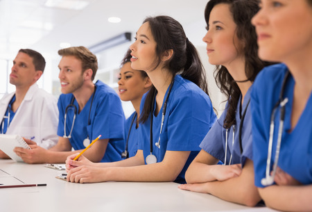 medicine and science: Medical students listening sitting at desk at the university Stock Photo
