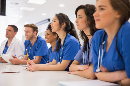 medicina: Los estudiantes de medicina escucha sentado en el escritorio en la universidad