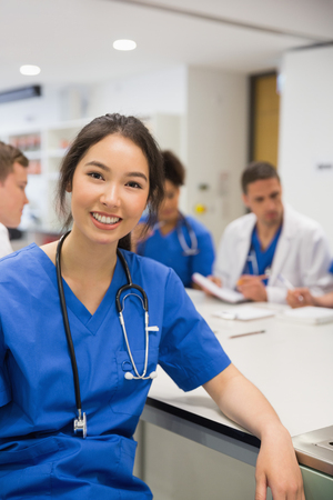 female student: Medical student smiling at the camera during class at the university Stock Photo