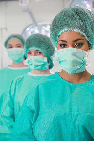 estudiantes medicina: Los estudiantes de medicina en sala de operaciones mirando a la c�mara en la universidad