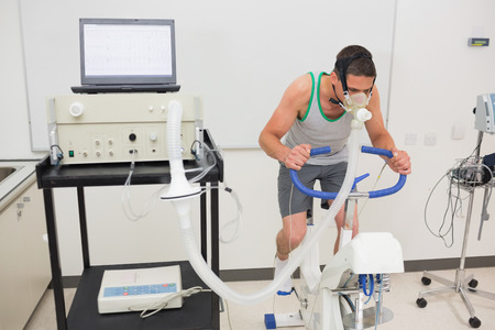 stress test: Man doing fitness test on exercise bike at the medical centre