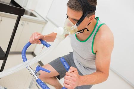 El hombre que hace examen de aptitud en bicicleta de ejercicio en el centro médico