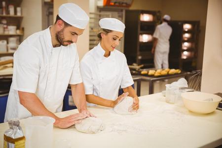 panadero: Equipo de panaderos amasan la pasta en una cocina comercial
