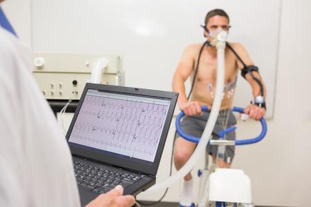 investigador cientifico: El hombre que hace examen de aptitud en bicicleta de ejercicio en el centro m�dico