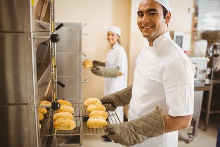 panadero: Baker, sonriendo a la cámara tomar rollos fuera del horno en una cocina comercial
