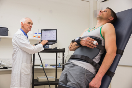 strapped: Man strapped to gurney to find out his BMR at the medical centre Stock Photo