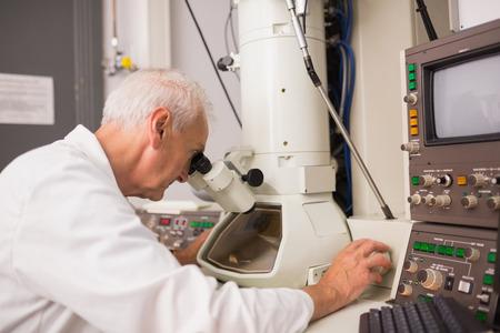 biochemist: Biochemist using large microscope and computer at the university Stock Photo