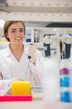 biochemist: Pretty science student using pipette at the university