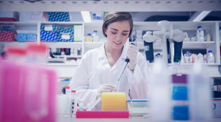 bata de laboratorio: Estudiante de ciencias bonita que usa la pipeta en la universidad Foto de archivo