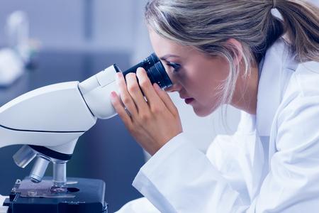 bata de laboratorio: Estudiante de la ciencia que mira a trav�s del microscopio en el laboratorio de la universidad