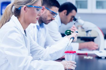 lab coat: Los estudiantes de ciencias que trabajan con productos qu�micos en el laboratorio de la universidad