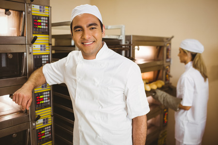 commercial kitchen: Handsome baker smiling at camera in a commercial kitchen Stock Photo