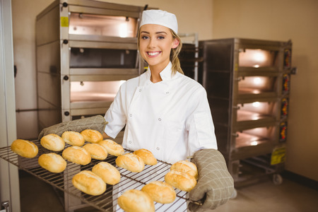 chef uniform: Baker smiling at camera holding rack of rolls in a commercial kitchen Stock Photo