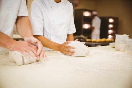 commercial kitchen: Team of bakers kneading dough in a commercial kitchen