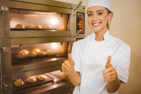 Baker smiling at camera beside oven in a commercial kitchen