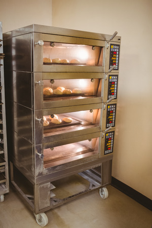 commercial kitchen: Bread rolls baking in oven in a commercial kitchen