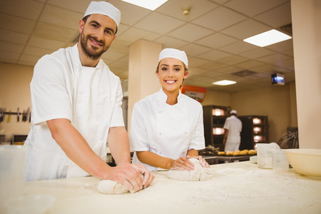 pastry chef: Team of bakers kneading dough in a commercial kitchen