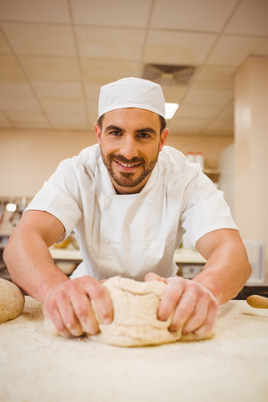 commercial kitchen: Baker kneading dough at a counter in a commercial kitchen