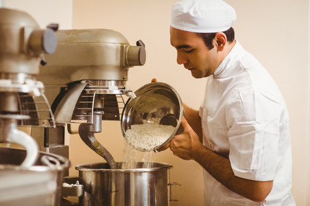 Baker pouring flour into large mixer in a commercial kitchen
