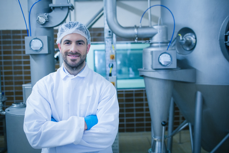 food processing: Food technician smiling at camera in a food processing plant Stock Photo