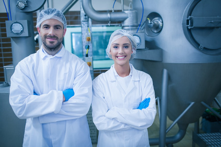 food industry: Food technicians smiling at camera in a food processing plant