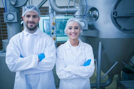 Technici voedsel lachend naar de camera in een levensmiddel verwerkingsbedrijf