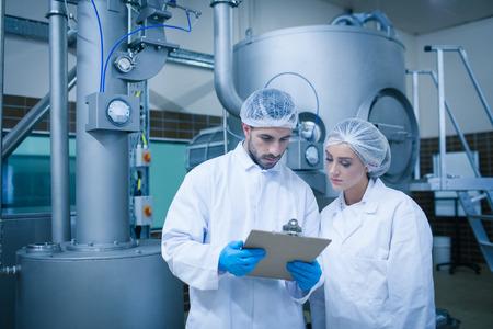 lacteos: T�cnicos de alimentos que trabajan juntos en una planta de procesamiento de alimentos