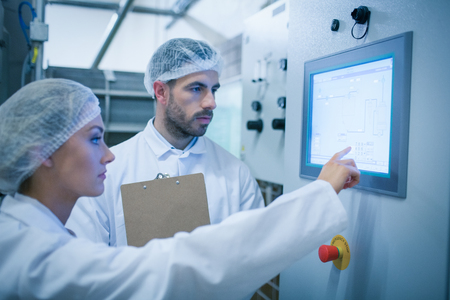 young plant: Food technicians working together in a food processing plant