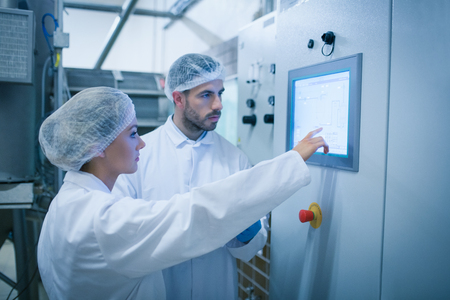 biotecnologia: Técnicos de alimentos que trabajan juntos en una planta de procesamiento de alimentos
