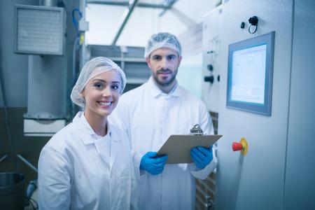 식품 가공 공장에서 함께 작동하는 식품 기술자 스톡 콘텐츠