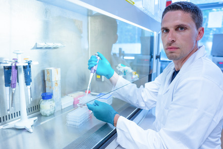 scientist man: Science student using pipette in the lab at the university