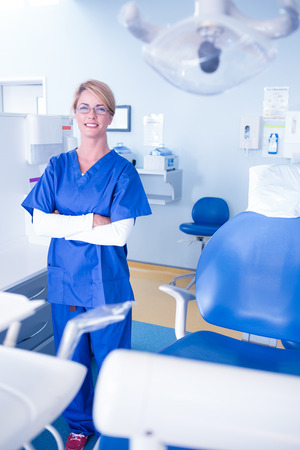 dental clinics: Smiling dentist standing with arms crossed at the dental clinic Stock Photo