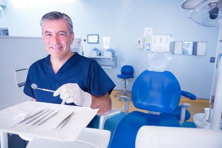 dentista: Dentista en batas de color azul sonriendo a la c�mara la celebraci�n de herramientas en la cl�nica dental