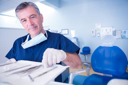 odontologo: Dentista recogiendo herramienta y sonriendo a la cámara en la clínica dental Foto de archivo
