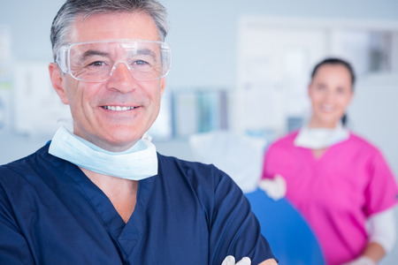 protective glasses: Smiling dentist with protective glasses at the dental clinic