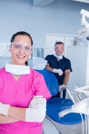 dental clinics: Smiling assistant and dentist behind her with protective glasses at the dental clinic